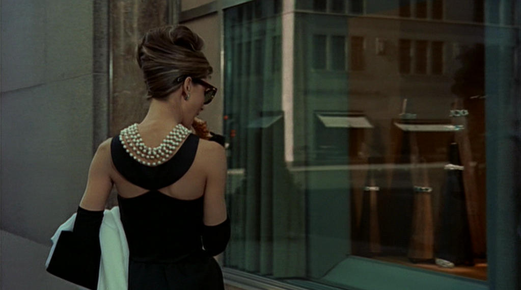 The necklace neatly falls down Hepburn's shoulders and back to emphasize the low-cut back of the dress. Jewelry in Movies