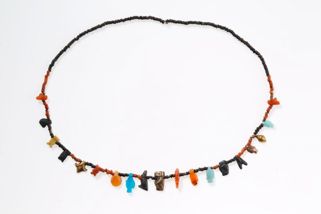 "Ancient Egyptian Jewelry Necklace with disc beads and amulets from the New Kingdom. This necklace is composed of tiny disk beads interspersed with a variety of amulets, including falcons, a frog, Tawerets, a lotus, bolti fish, a shell or bullae, a hand, and a ""nefer"" sign. Some amulets, such as the lotus, frog, and fish, symbolize fertility, while Taweret and the falcon offer protection. The ""nefer"" hieroglyph conveys a good wish. This necklace was one of three stored in a small jewelry box in a man's burial. Carnelian, gold, silver, faience, glass, yellow stone, tin"