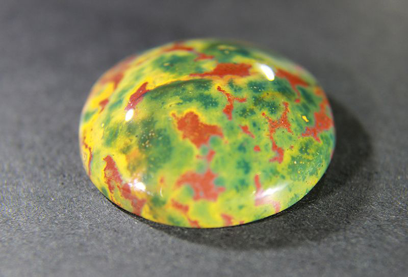A colorful cabochon of Bloodstone, a variety of Chalcedony from India, is also known as Heliotrope. This bloodstone has olive-green, orange and brick-red highlights.
