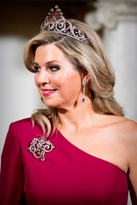The Dutch Queen Maxima wears diamond and ruby oversize brooch, elegant drop earrings, and a spectacular tiara.